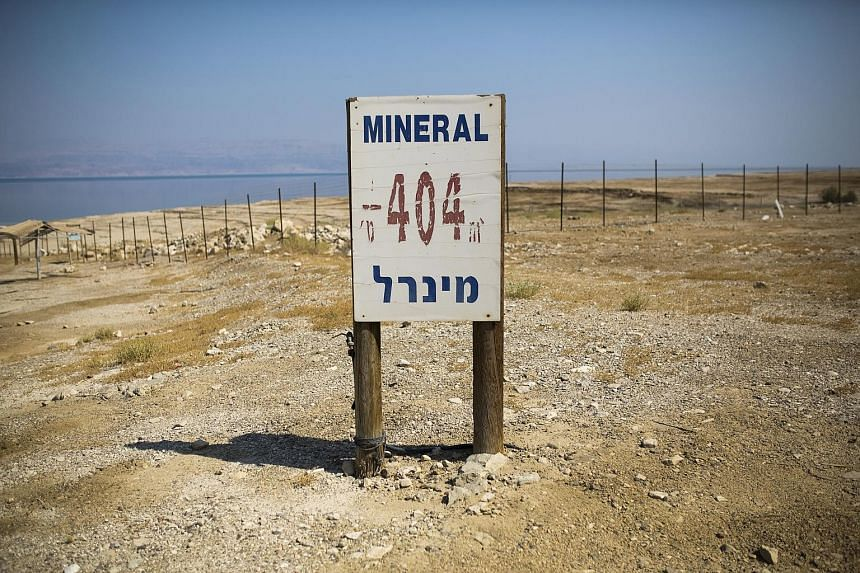 Sinkholes seen on the shore of the Dead Sea and a sign (above) at an abandoned resort showing its elevation of 404m below sea level. The Dead Sea has been shrinking by more than a metre a year in recent decades due to damming and unsustainable uses o