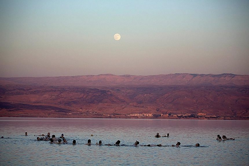 Ultra-Orthodox Jewish men floating (above) in the water and covering themselves in mud at a males-only beach in the northern part of the Dead Sea. The mineral-rich water of the Dead Sea has been known to have therapeutic qualities - such as assisting