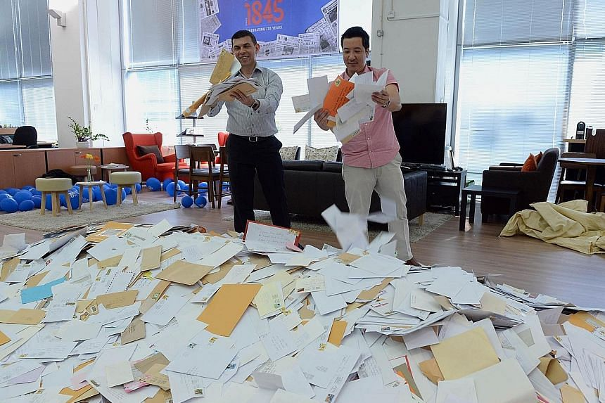 ST editor Warren Fernandez (far left) and sports editor Marc Lim picking entries from the almost 65,000 received. One winner will be drawn from the shortlist of 2,000 for the Land Rover Discovery Sport vehicle, which is the ST170 Treats contest's big