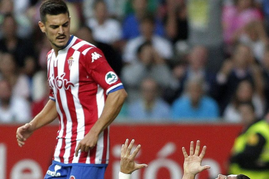 Sporting Gijon's players like Isma Lopez (left) are not overawed by Real Madrid's stars like Cristiano Ronaldo as they hold out for a goalless draw, heaping pressure on new Real manager Rafael Benitez.