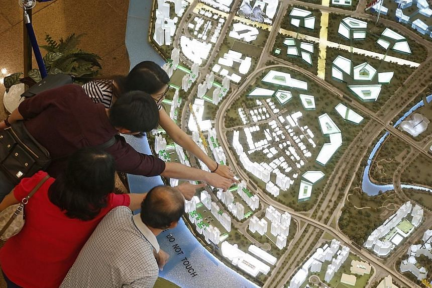 People viewing models of housing projects on sale, at the HDB Hub yesterday. From yesterday, the income ceiling for Singaporean households to buy new flats and ECs was raised by $2,000, to $12,000 and $14,000 respectively.