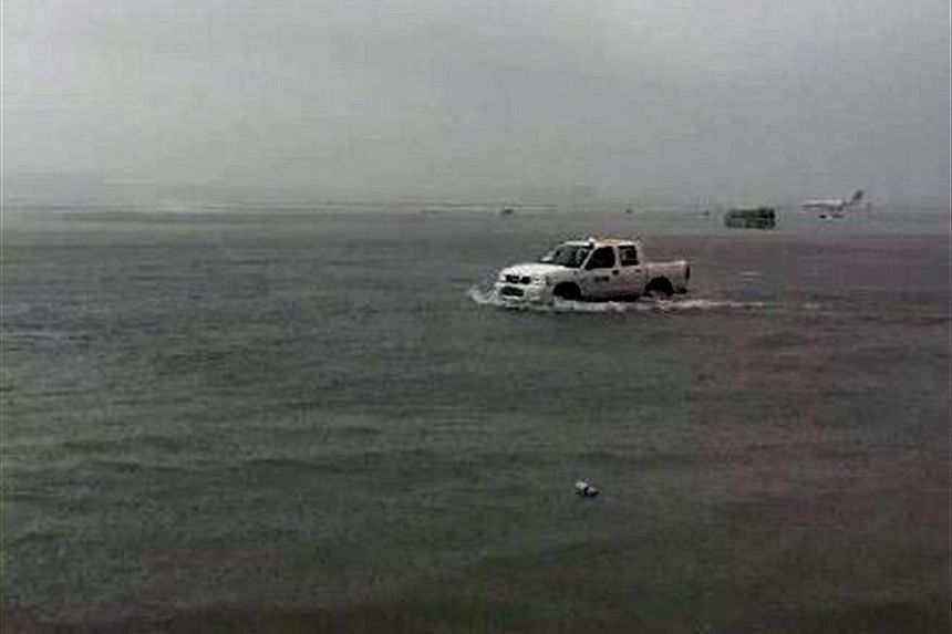 An airport vehicle making its way across a flooded runway at Hongqiao International Airport (above), while people try to stay dry (left) in flooded areas of Shanghai after the combined effect of Typhoon Goni and a cold front caused heavy downpours.