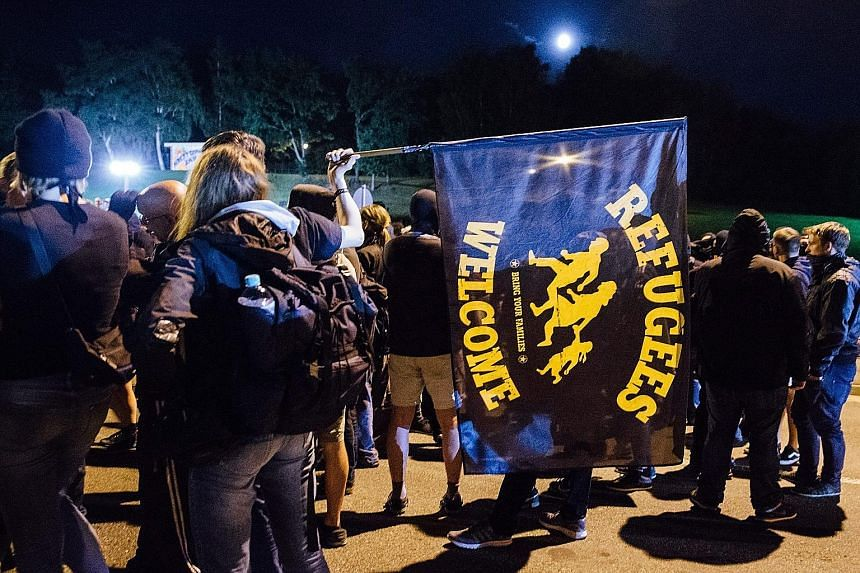 Protests by right-wing Germans - many in hoods - at an emergency shelter for refugees in Heidenau over the weekend turned violent. More than 30 police officers were injured in clashes when the protesters started pelting law enforcers with bottles and
