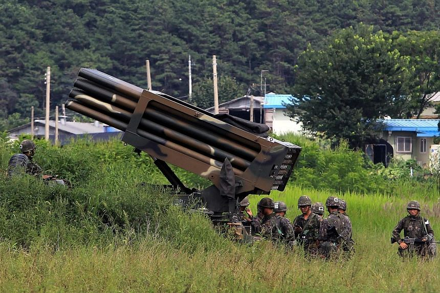 South Korean soldiers setting up a multiple launch rocket system yesterday in Yeoncheon. Despite the military activity, civilian life in the South remains unchanged, with many immune to the North's recurring threats.