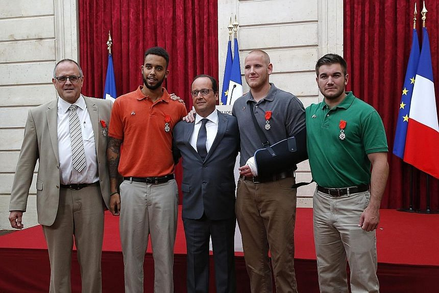 French President Francois Hollande with (from left) Mr Chris Norman, Mr Anthony Sadler, Mr Spencer Stone and Alek Skarlatos, who received Legion d'Honneur medals.