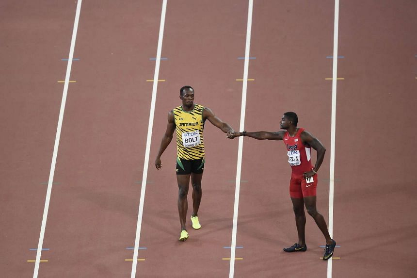 Usain Bolt (left) bumps fists with Justin Gatlin before competing in the final of the men's 100m athletics event at the 2015 IAAF World Championships on Aug 23, 2015.