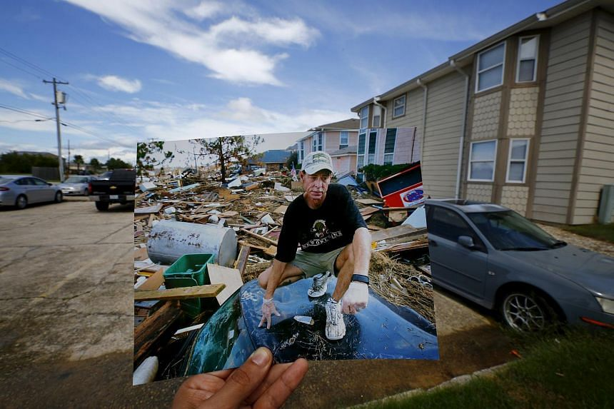 Photographer Carlos Barria holds a print of a photograph he took in 2005, as he matches it up at the same location 10 years on, in North Shore, northwest of New Orleans, United States on Aug 17, 2015.