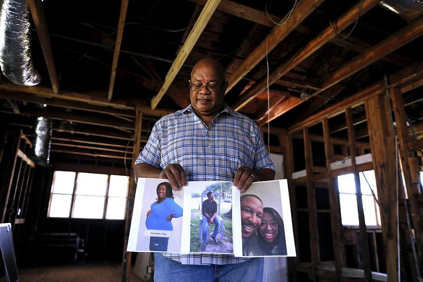 In this posed photograph Charles Brown holds pictures of his children, who have not moved back to New Orleans since Hurricane Katrina, inside his home in the Gentilly neighbourhood of New Orleans, Louisiana on Aug 1, 2015.