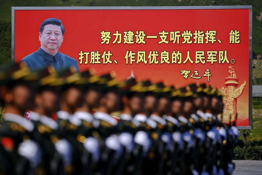 A picture of Chinese President Xi Jinping is seen on a billboard behind soldiers of China's People's Liberation Army marching during a training session for a military parade to mark the 70th anniversary of the end of World War Two, at a military base