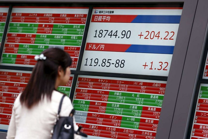 A woman looks at screens displaying, stock quotes, the Nikkei average and the Dollar to Yen exchange rate outside a brokerage in Tokyo on Aug 25, 2015.