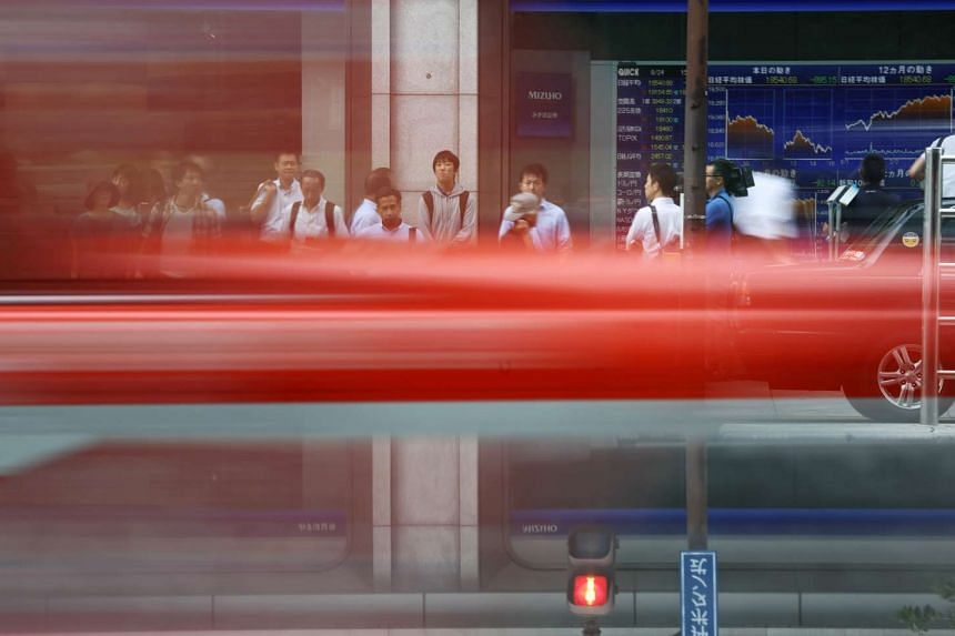 A taxi passes as pedestrians wait to cross a road in front of an electronic stock board outside a securities firm in Tokyo, Japan, on Monday, Aug. 24, 2015.