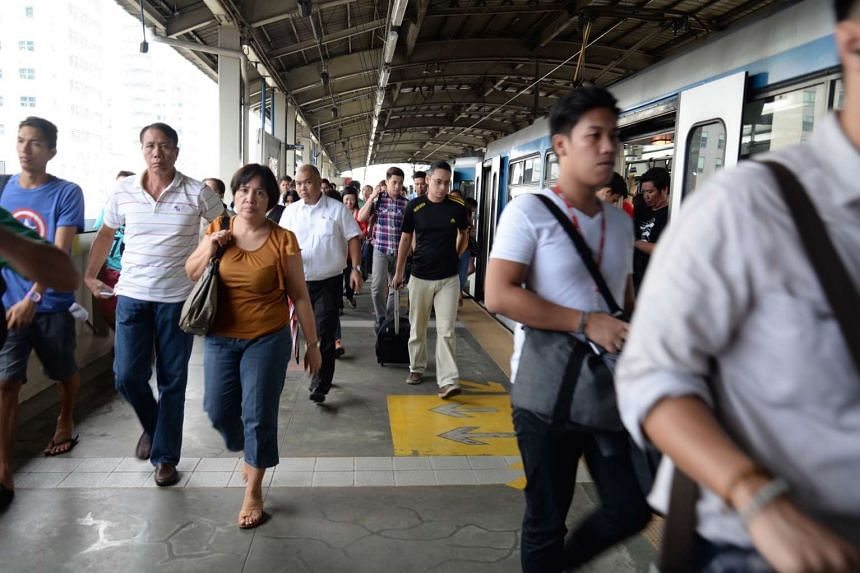 People disembarking from a train at the Quezon Avenue station of the MRT in Manila.