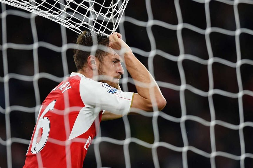 Arsenal's Aaron Ramsey looks dejected as he holds onto the goal net.