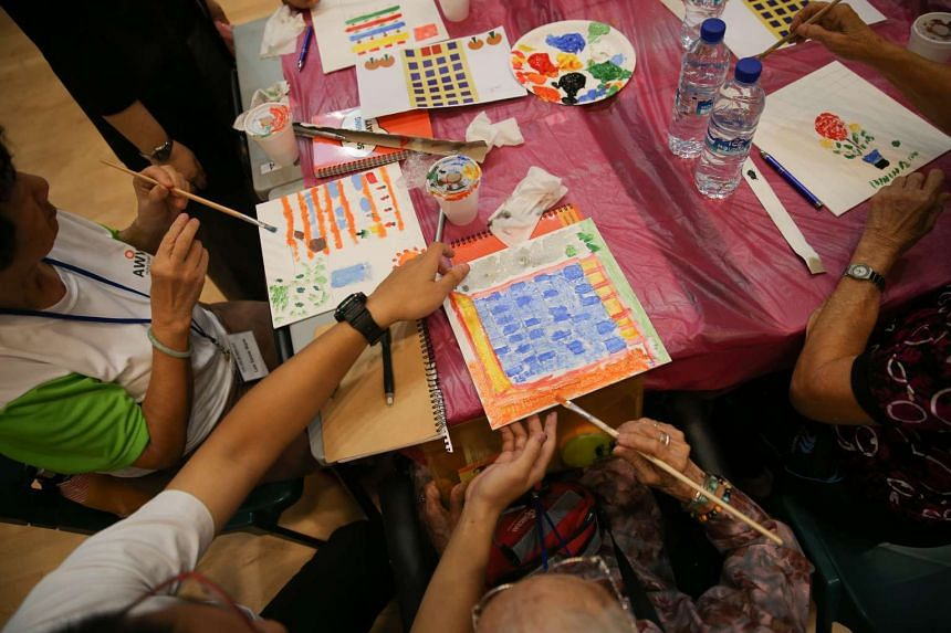 A student from ITE College Central helping a senior from Thye Hua Kwan Seniors Activity Centre with painting.