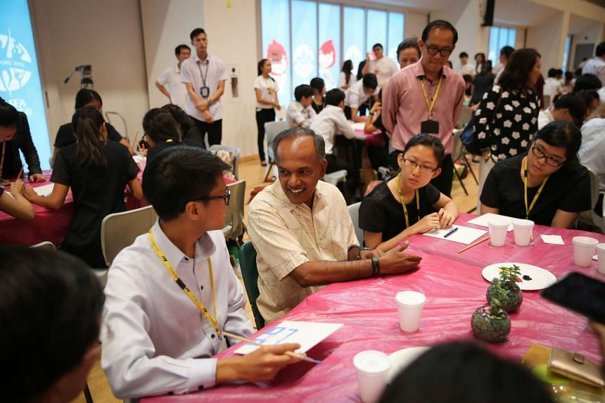 Mr K. Shanmugam speaking with students involved in the mass painting event.