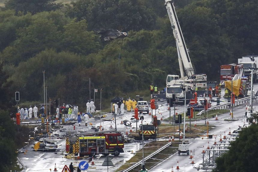A crane removes the remains of a Hawker Hunter fighter jet that crashed onto the A27 road at Shoreham near Brighton in Britain on Monday.