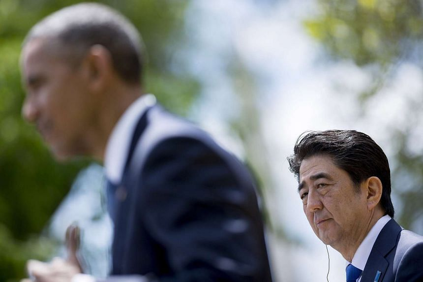 Mr Shinzo Abe looks on as President Barack Obama speaks during a joint news conference in the Rose Garden of the White House in Washington, DC, US.