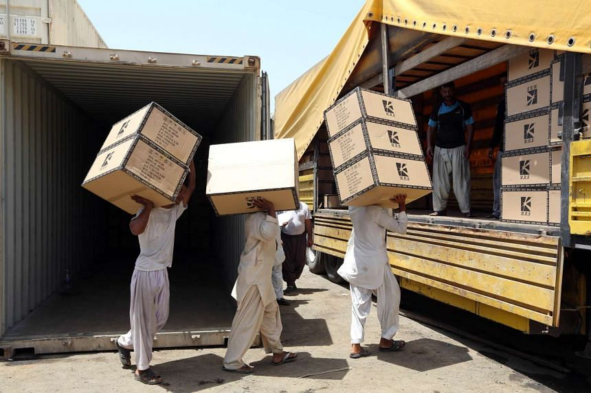 Iranian workers transferring goods from a cargo container to trucks at the Kalantari port in city of Chabahar on May 12, 2015.