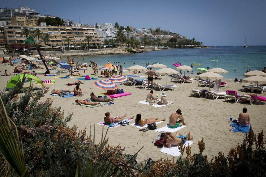 People swimming and sunbathing on the Figueretes Beach on Ibiza island, Spain.