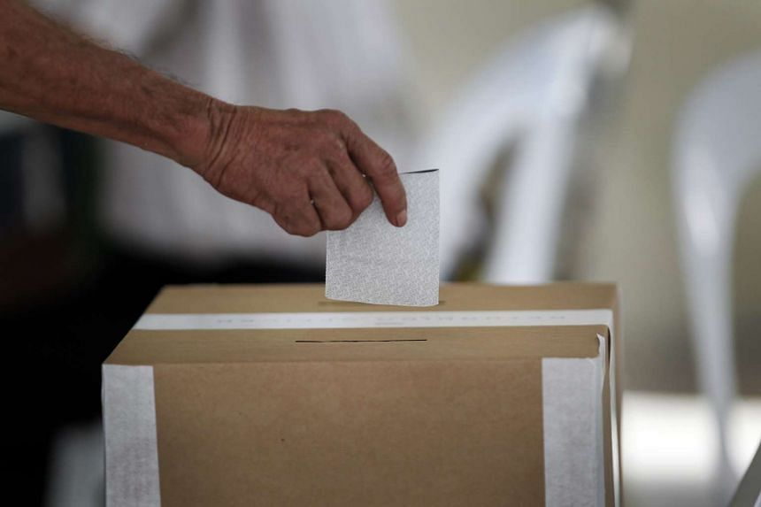 A voter casting his ballot on Polling Day in 2011.
