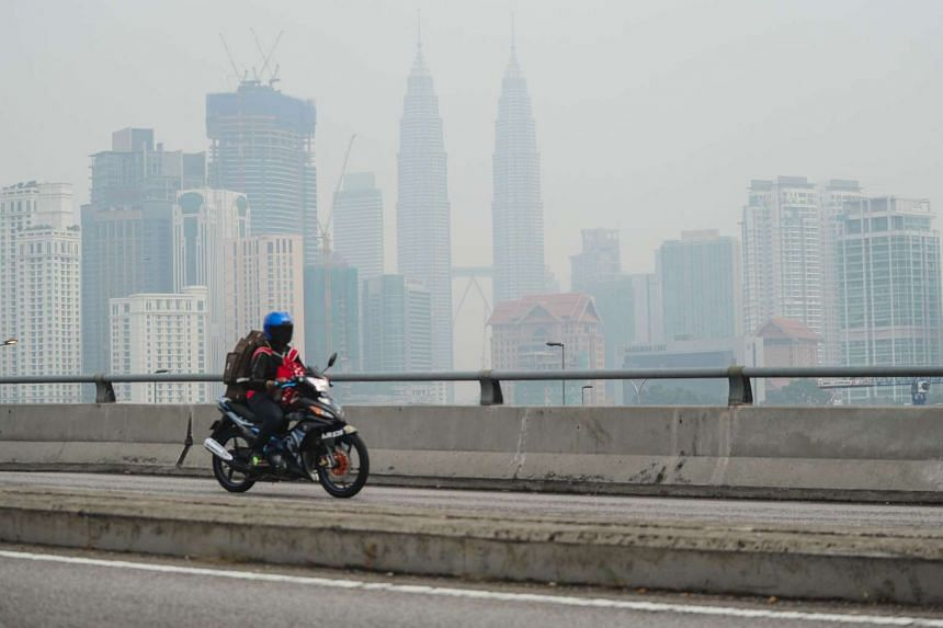 A man rides his bike as Malaysia's landmark Petronas Twin Towers are seen obscured by haze in Kuala Lumpur on Aug 24, 2015.