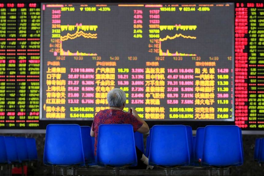 An investor looking at an electronic board showing stock information at a brokerage house in Shanghai on Aug 25, 2015.