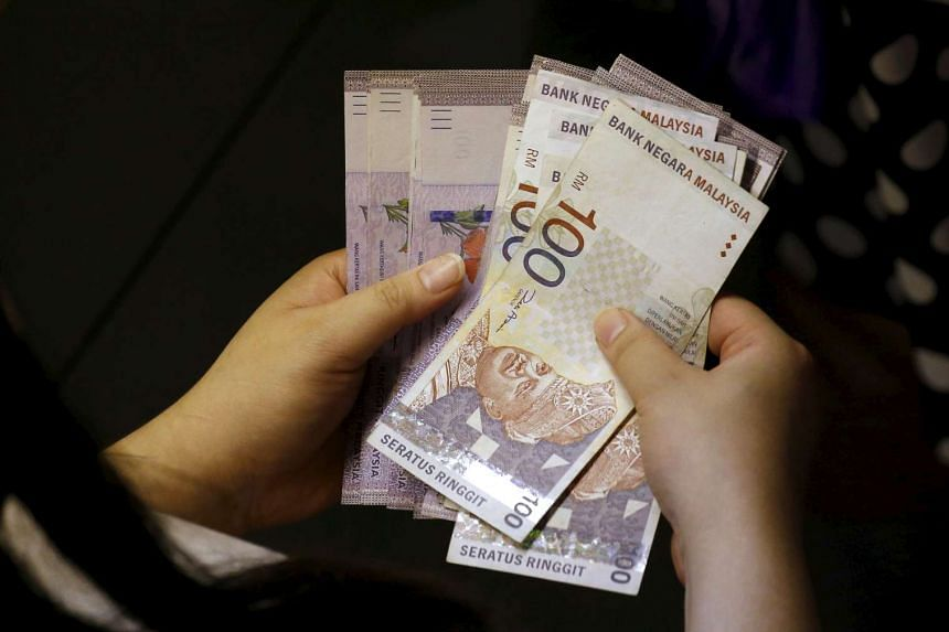 A customer counting ringgit notes outside a money changer on Aug 25, 2015.