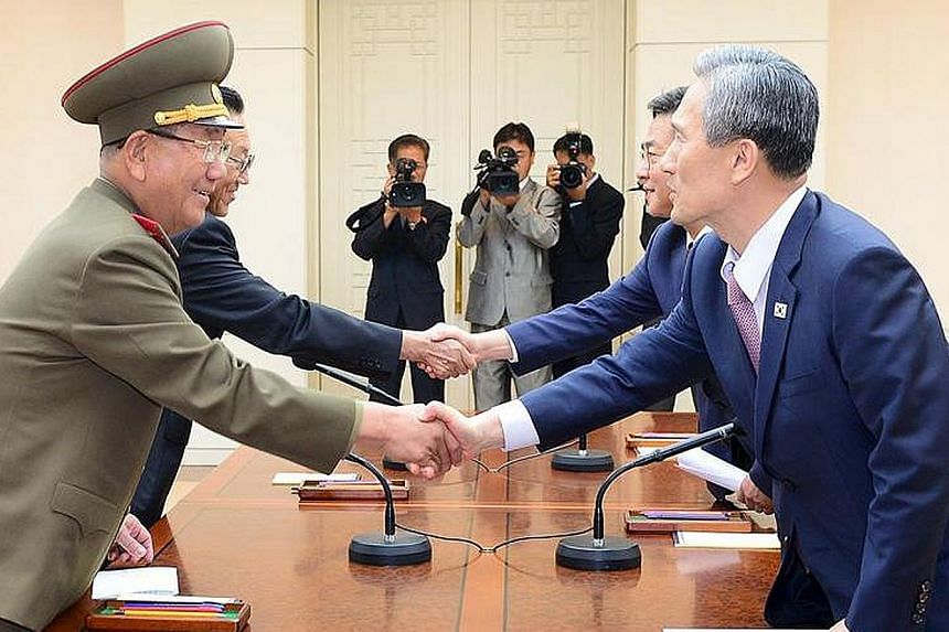 South Korean National Security Adviser Kim Kwan Jin (right) shaking hands with Mr Hwang Pyong So (left), the top military aide to North Korean leader Kim Jong Un, after talks in Panmunjom, in this photo released yesterday.