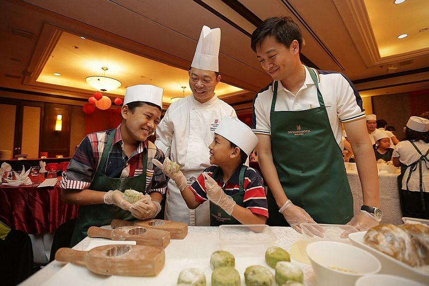 Muhammad Izzat Mohd Ismail (left) and Zulqarnain Mohd Zainuddin, both nine, having a fun time learning to make snowskin mooncakes. They were among 20 kids from the Singapore Children's Society being treated by Hong Leong Foundation to a mooncake-maki