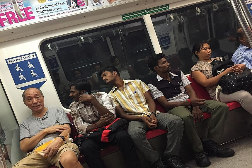 Top: Mr Saravanan breaking into a smile after Mr Lau told him and two other foreign construction workers that they did not have to give up their train seats to men. Above: The selfie taken by Mr Saravanan.