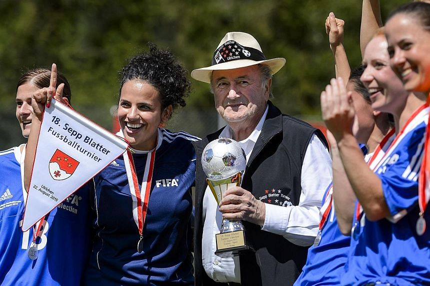 Outgoing Fifa president Sepp Blatter (centre), posing with players and holding the trophy for the Sepp Blatter Tournament, in Ulrichen, his hometown, last Saturday.