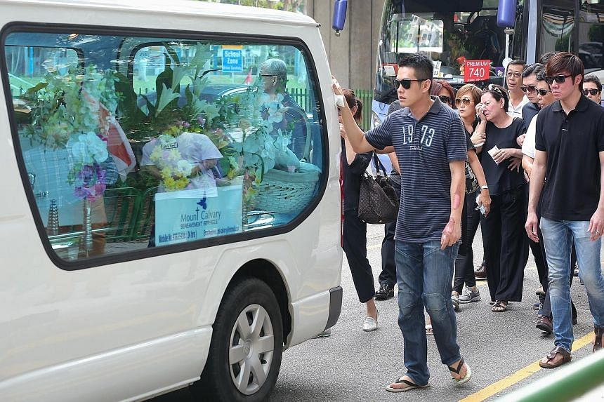 Mr Ng Su Teck (left), with his arm still bearing burn scars, behind the hearse carrying his wife's coffin. The cortege was leaving New Upper Changi Road yesterday morning.