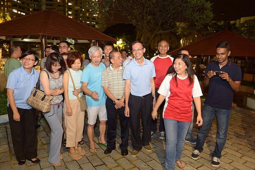 (Above) Mrs Jeannette Chong-Aruldoss (second from right) of the Singapore People's Party and Mr Yee Jenn Jong (fourth from right, in blue shirt) of the Workers' Party at a gathering at Mandarin Gardens with their supporters.