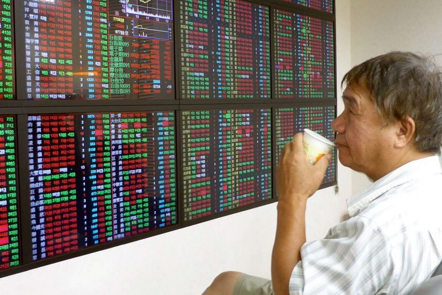 A man drinks water while watching the Taiwan Stock Exchange (TAIEX) data on an electronic board at a brockerage in Taipei, Taiwan, 26 August 2015. PHOTO: EPA