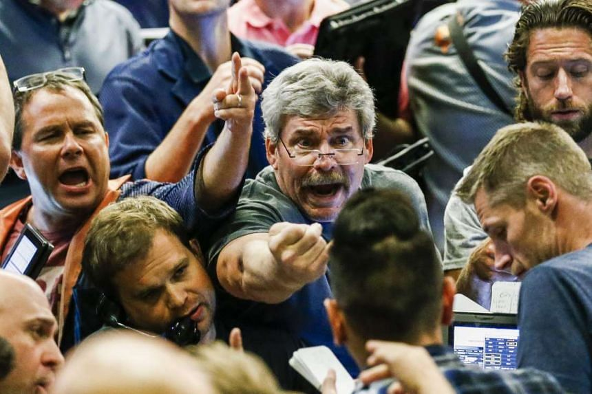 Traders shouting out their orders as they work in the S&P 500 options pit at the Chicago Board Options Exchange. US Dow Jones industrial average was up 2% at open on Wednesday. PHOTO: EPA