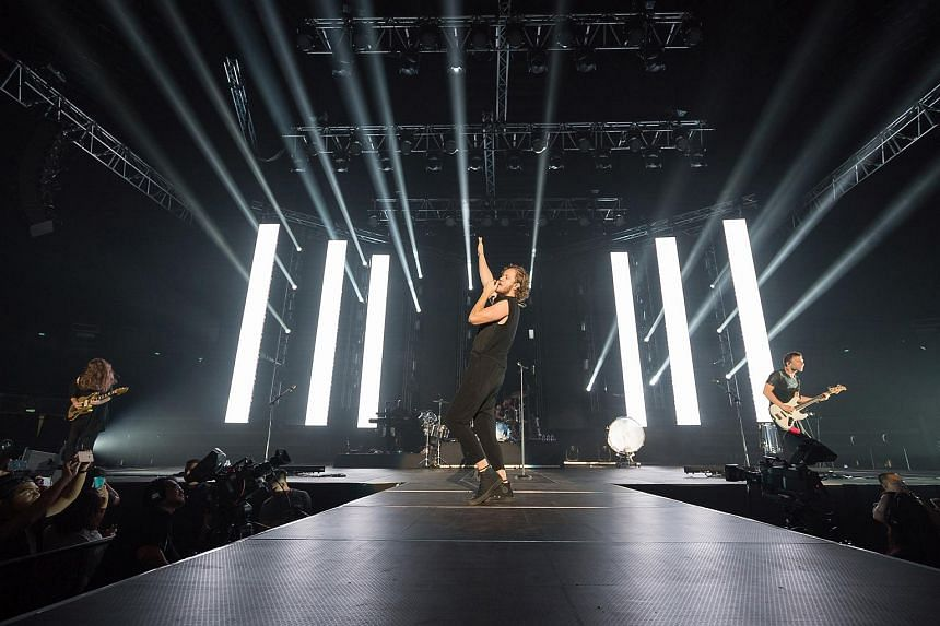Imagine Dragons frontman and lead vocalist Dan Reynolds (centre) performing at the Singapore Indoor Stadium.