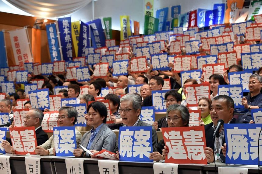 """Lawyers and scholars hold placards saying """"violation of the constitution"""" and """"scrap security bills"""" during a press conference in Tokyo on Aug 26, 2015."""