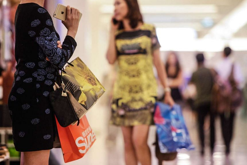 A shopper holding her shopping bags as others walk through the Siam Paragon shopping mall in Bangkok, Thailand.