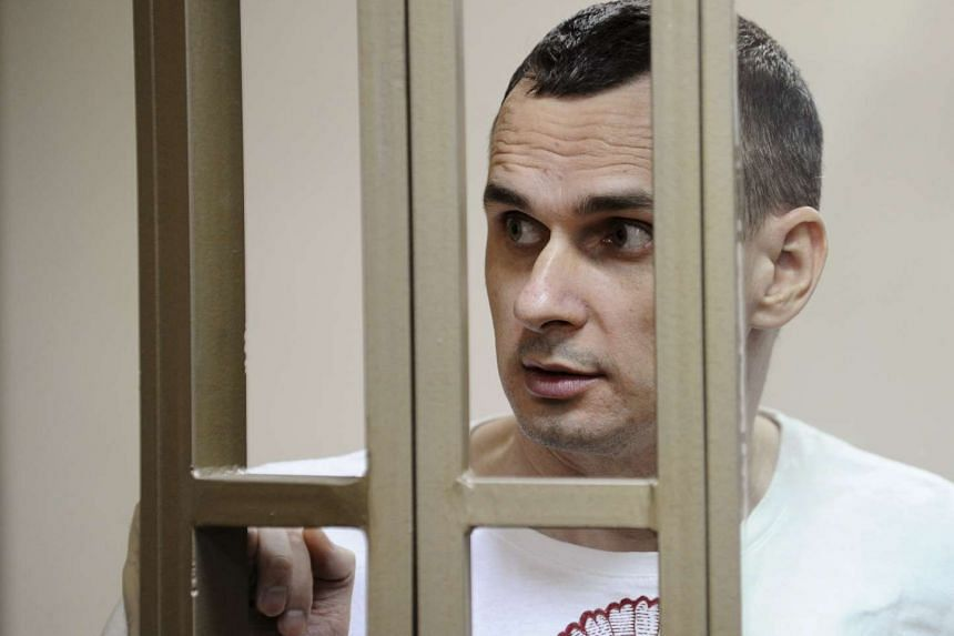 Ukrainian film director Oleg Sentsov looks on from a defendants' cage as he attends a court hearing in Rostov-on-Don, Russia on Tuesday where he was  sentenced Sentsov to 20 years in a high-security penal colony.