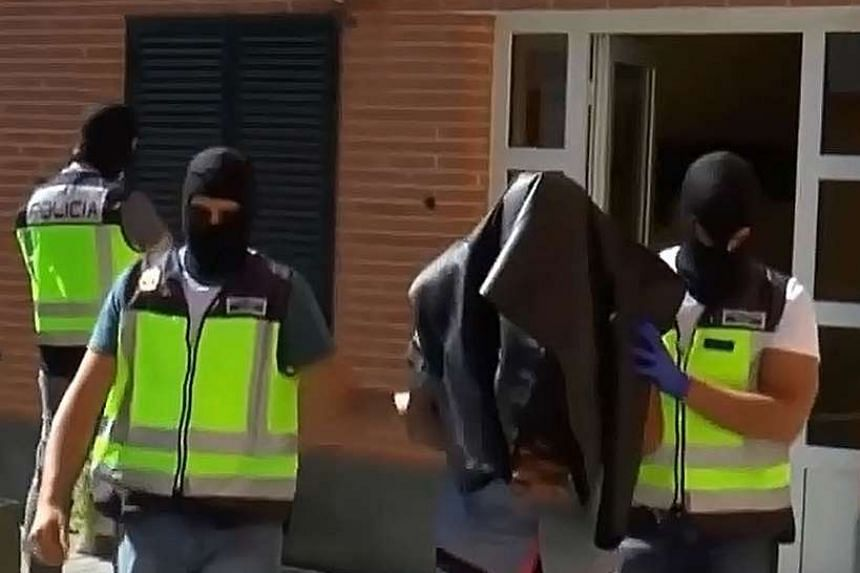 A person suspected of forming part of a network that recruited and sent fighters to the Islamic State group, being led away by Spanish police in San Martin de la Vega, about 30 kilometres south of Madrid in a video grab released by the Spanish Interi