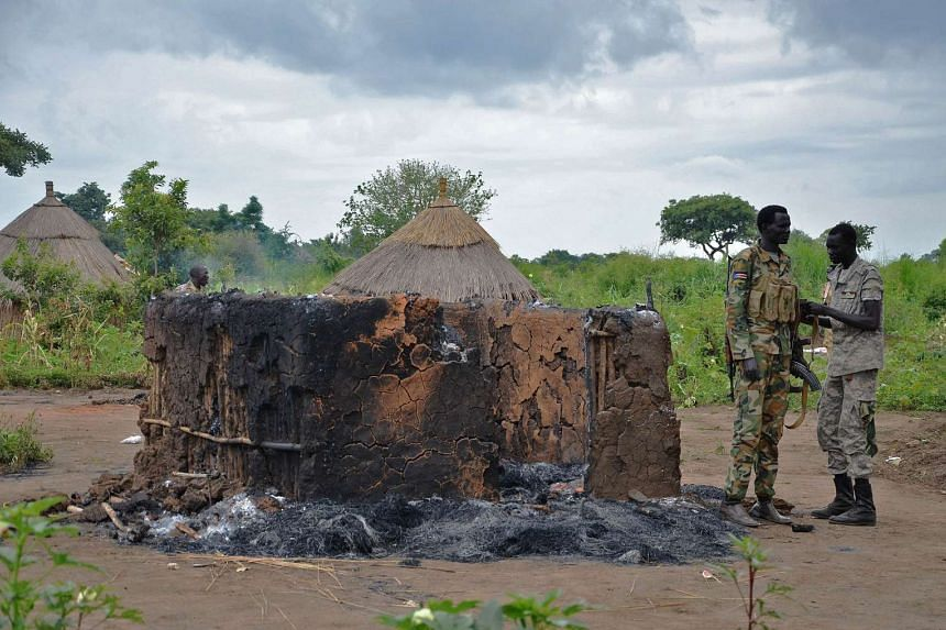 South Sudanese SPLA soldiers stand near a burned out hut in Pageri in Eastern Equatoria state on August 20, 2014.