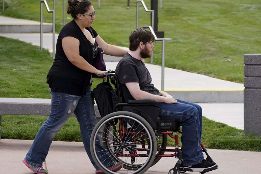 Aurora theatre shooting victim Caleb Medley (in wheelchair) arrives with his wife Katie (pushing him) at the Arapahoe County Courthouse in Centennial, Colorado on July 16, 2015 to hear the verdict in the trial.