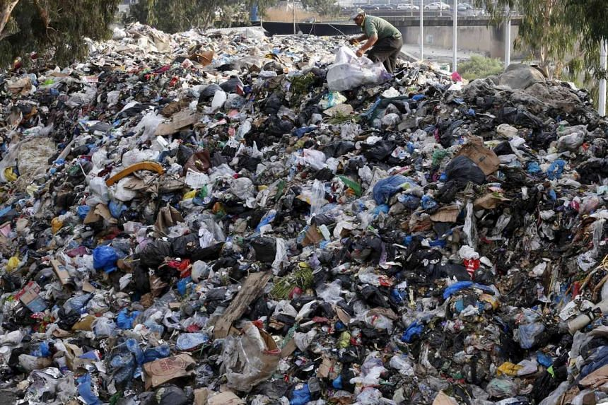 A scavenger on top of a pile of garbage by the Beirut River in Lebanon on Monday. Protest organisers have called for a fresh demonstration against the government after a weekend of rallies in central Beirut turned violent and left scores of people in