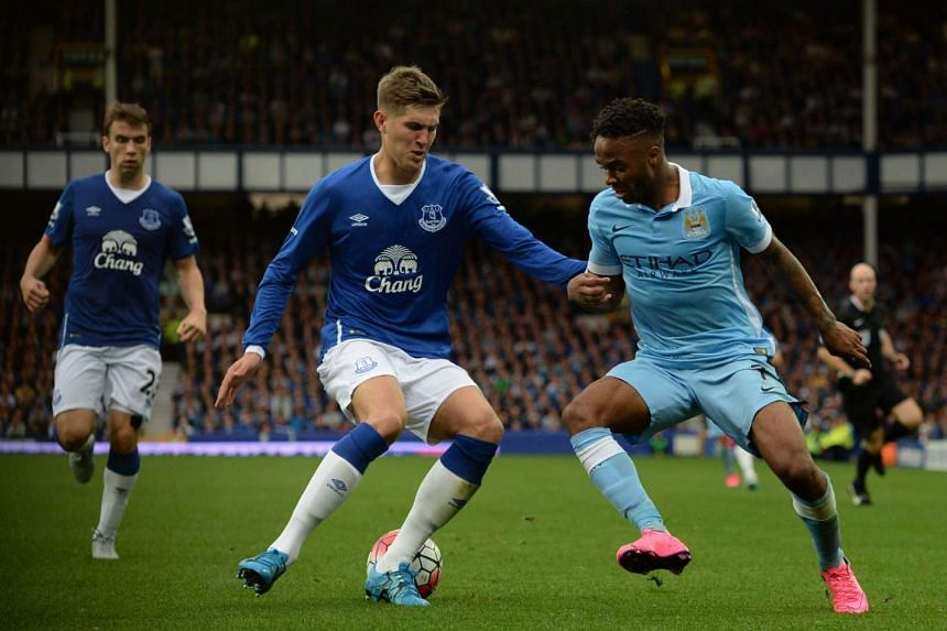Everton's John Stones (left) vies with Manchester City's Raheem Sterling on Aug 23, 2015.