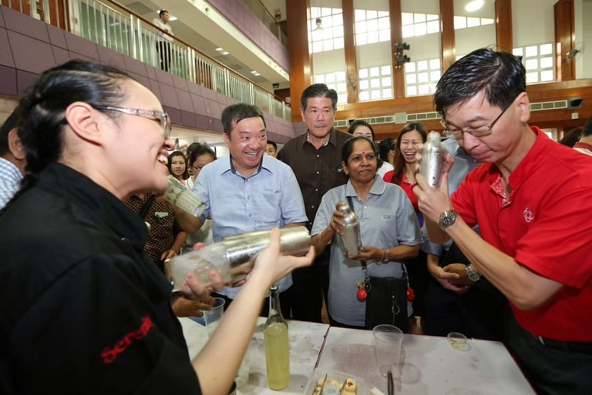 Bartender Stephenie Felita (extreme left, in black), 23, teaching Potong Pasir grassroots adviser Sitoh Yih Pin (second from left), Madam Thalmalmulayee Maniam (third from right), 65, and People's Association CEO Ang Hak Seng (extreme right, in red)