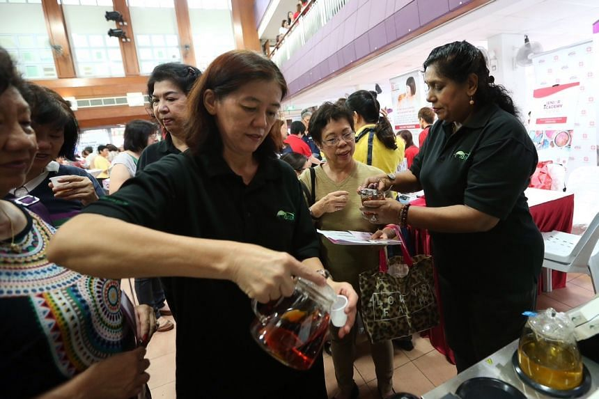 63-year-old Indira Thevy (extreme right) serving customers at the Teas Ideas booth during the Senior Academy Golden Work Series showcase at Potong Pasir Community Club on Aug 27.