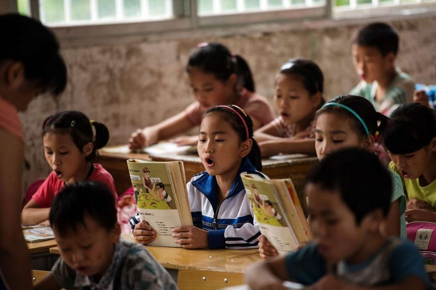 Children reading in a classroom at Xianghe Primary School in the town of Xianghe.