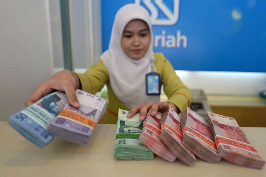 A bank employee displaying bundles of Indonesian rupiah notes in Jakarta on Aug 25.