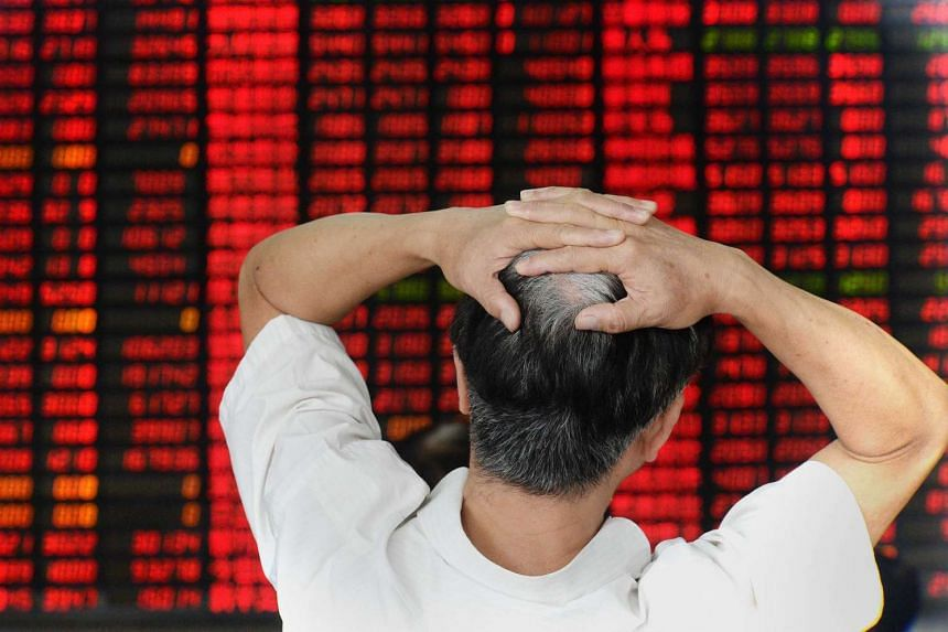 An investor checking share prices at a securities firm in Shanghai on Aug 26, 2015.