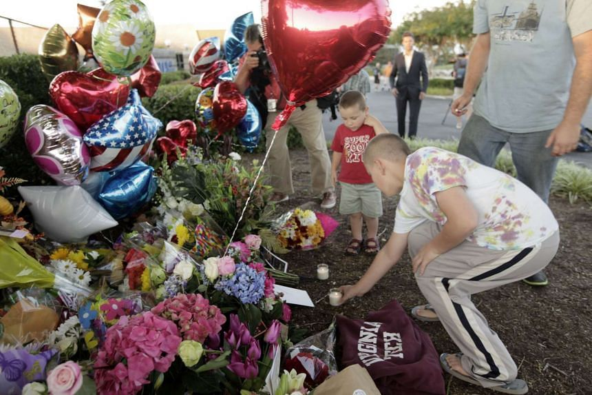 People bring flowers and candles to a memorial for the two journalists who were killed during a live broadcast on Aug 26, 2015 in Roanoke, Virginia.